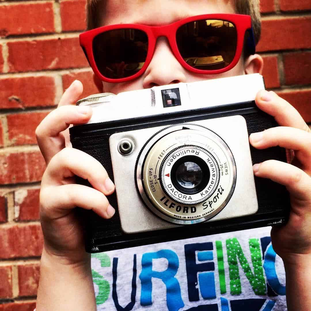 LITTLE BOY IN RED SUNGLASSES HOLDING UP VINTAGE CAMERA.
