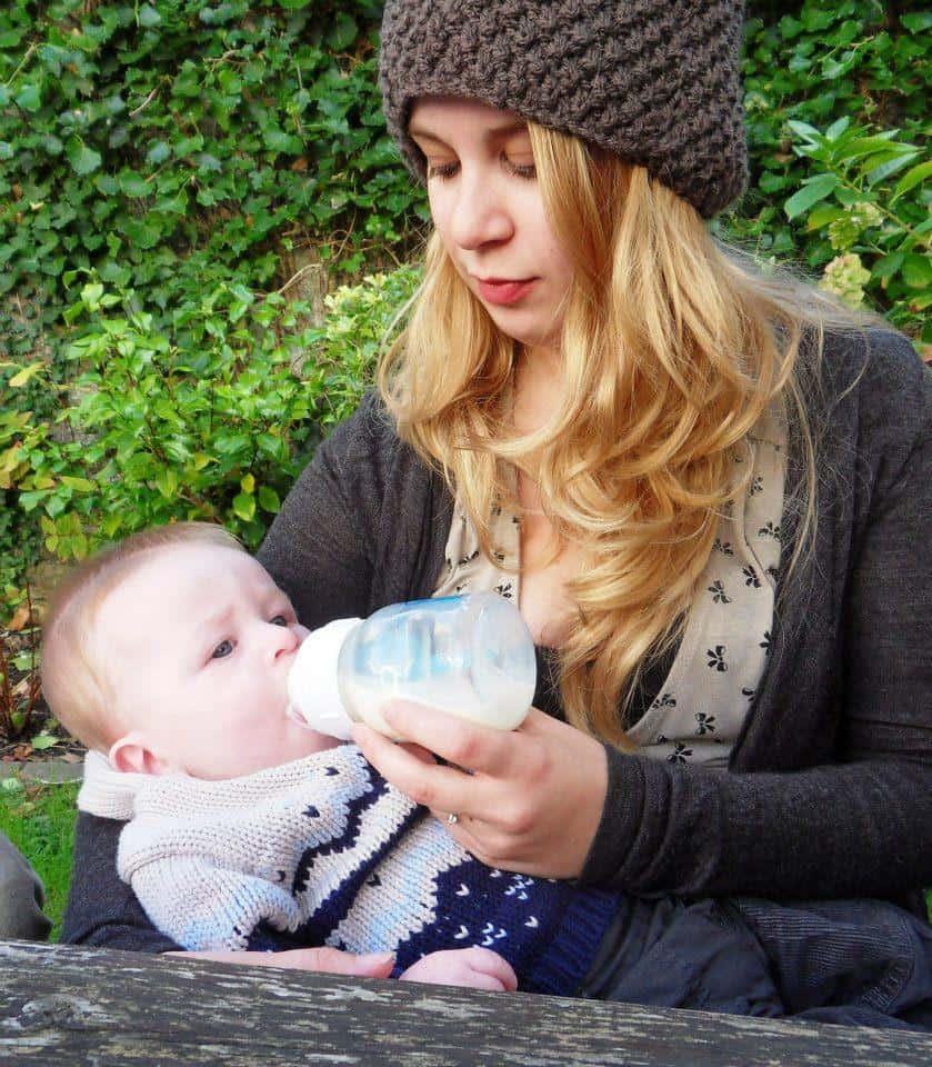 Awoman bottlefeeding her baby