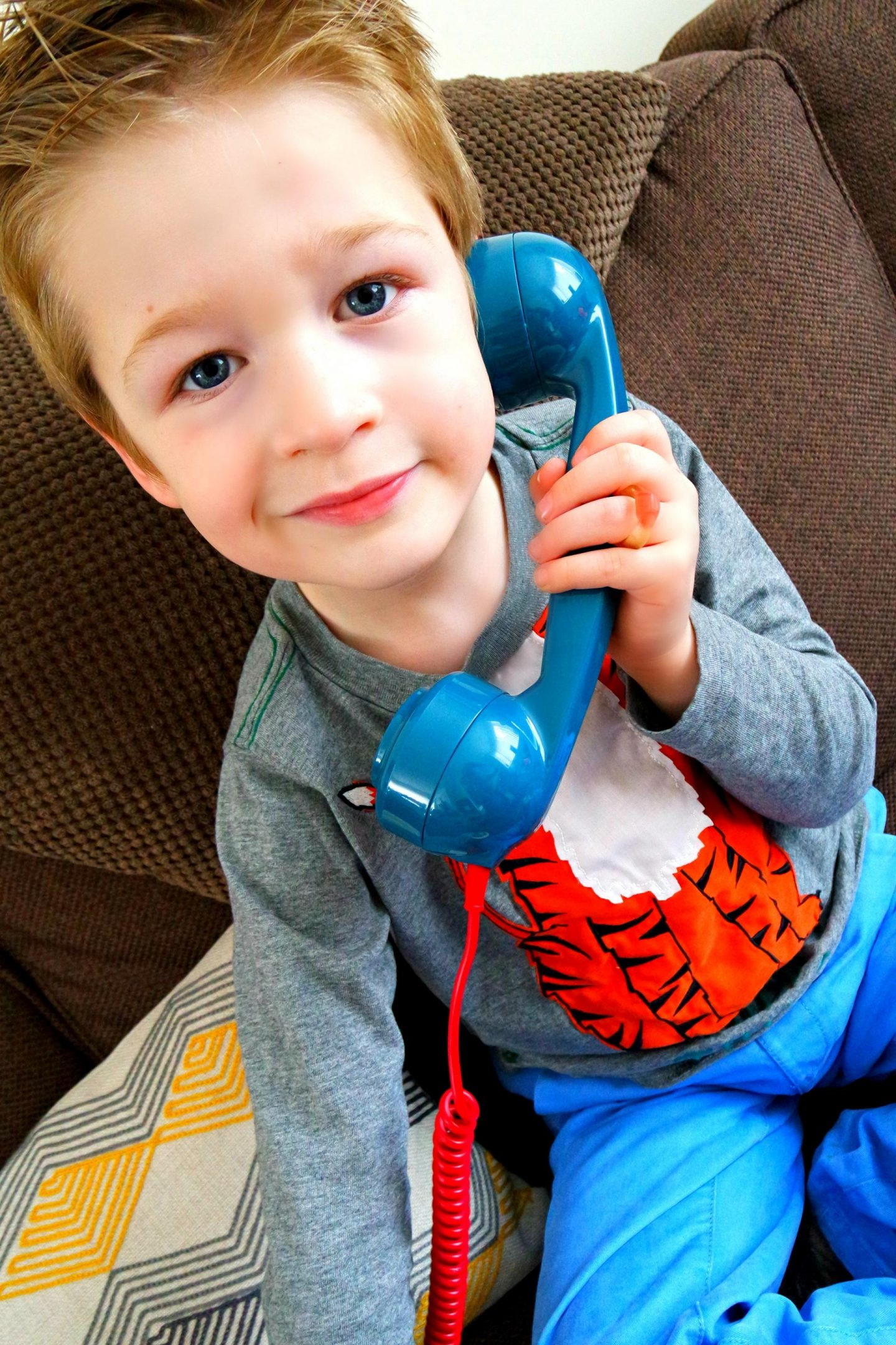 Little boy on a blue phone