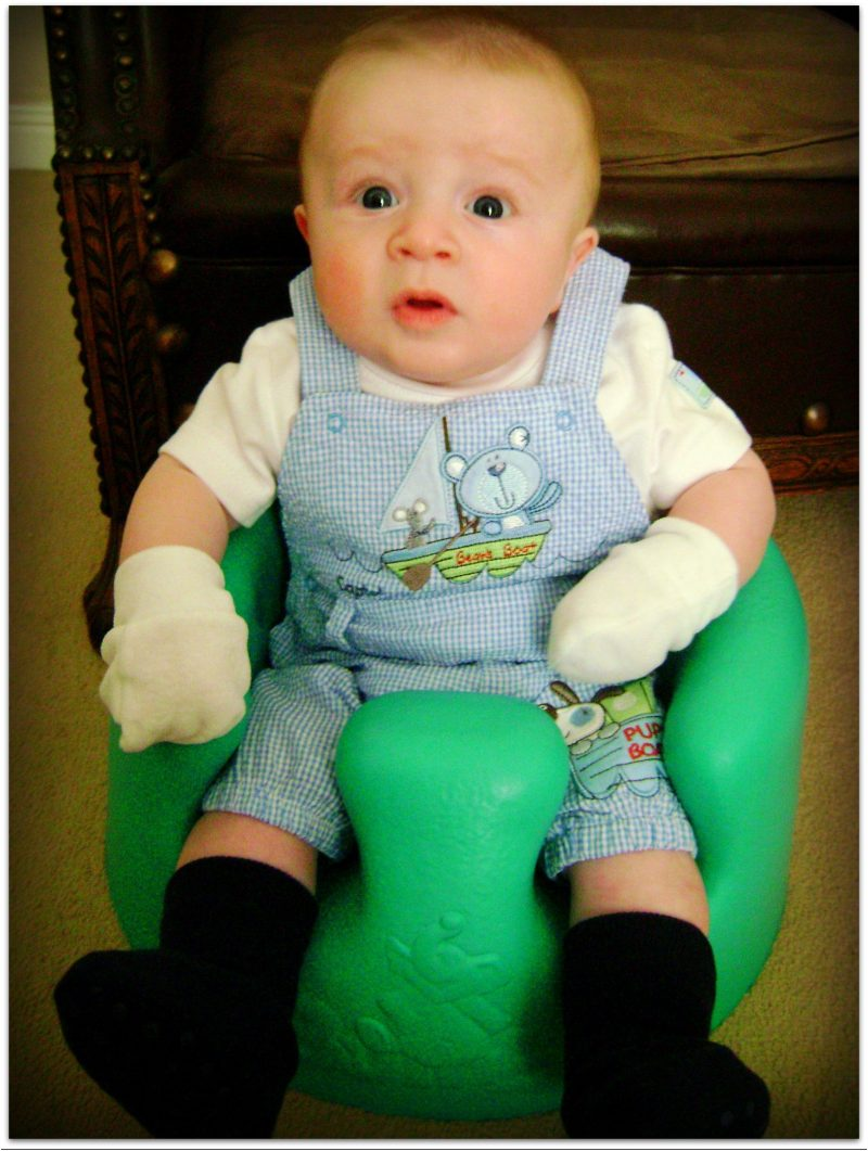 Baby sitting in a bright blue bumbo pulling a really shocked face at the camera