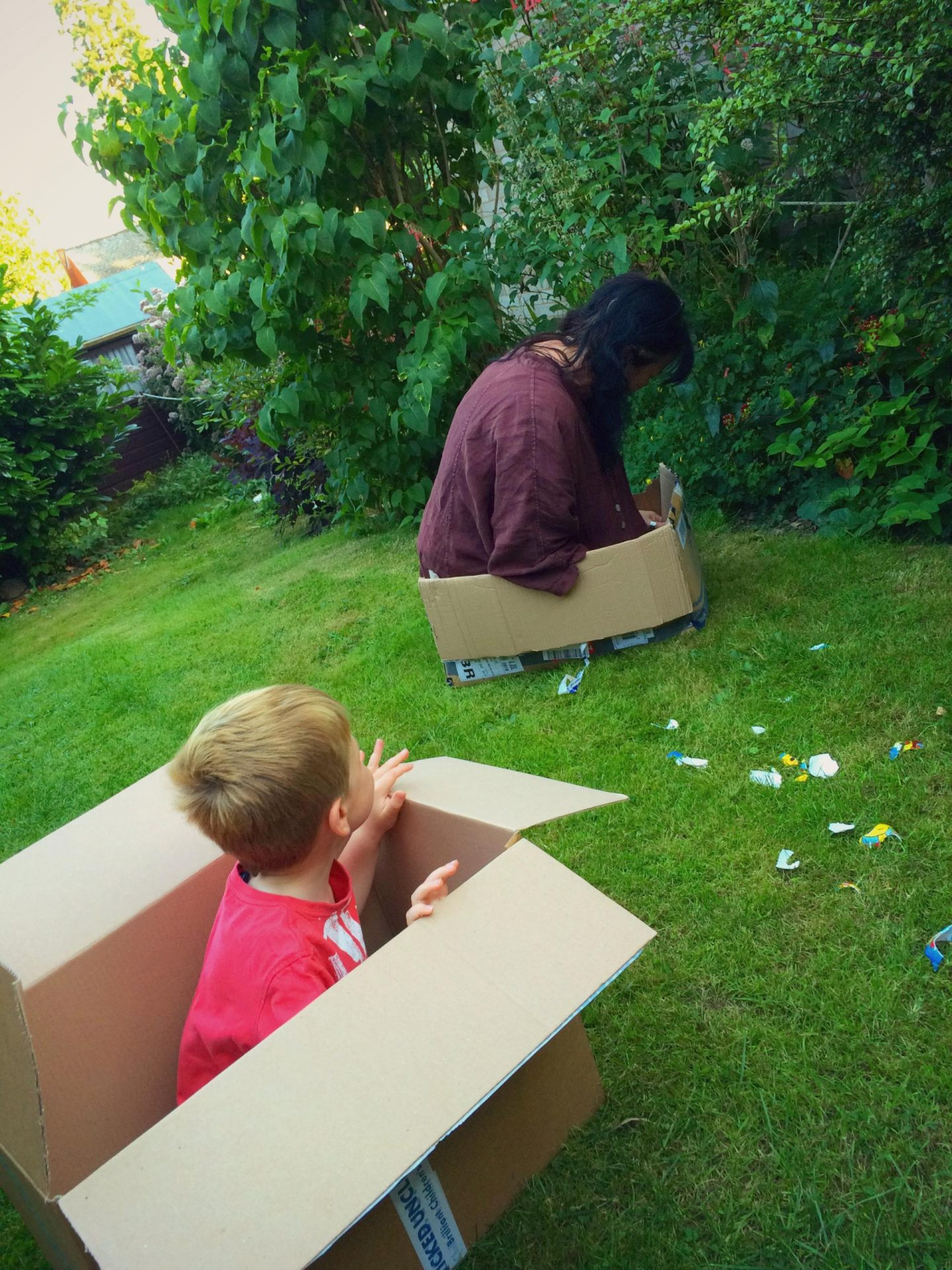 Photo of a child sitting in a cardboard box with his nanny next to him also in a cardboard box.
