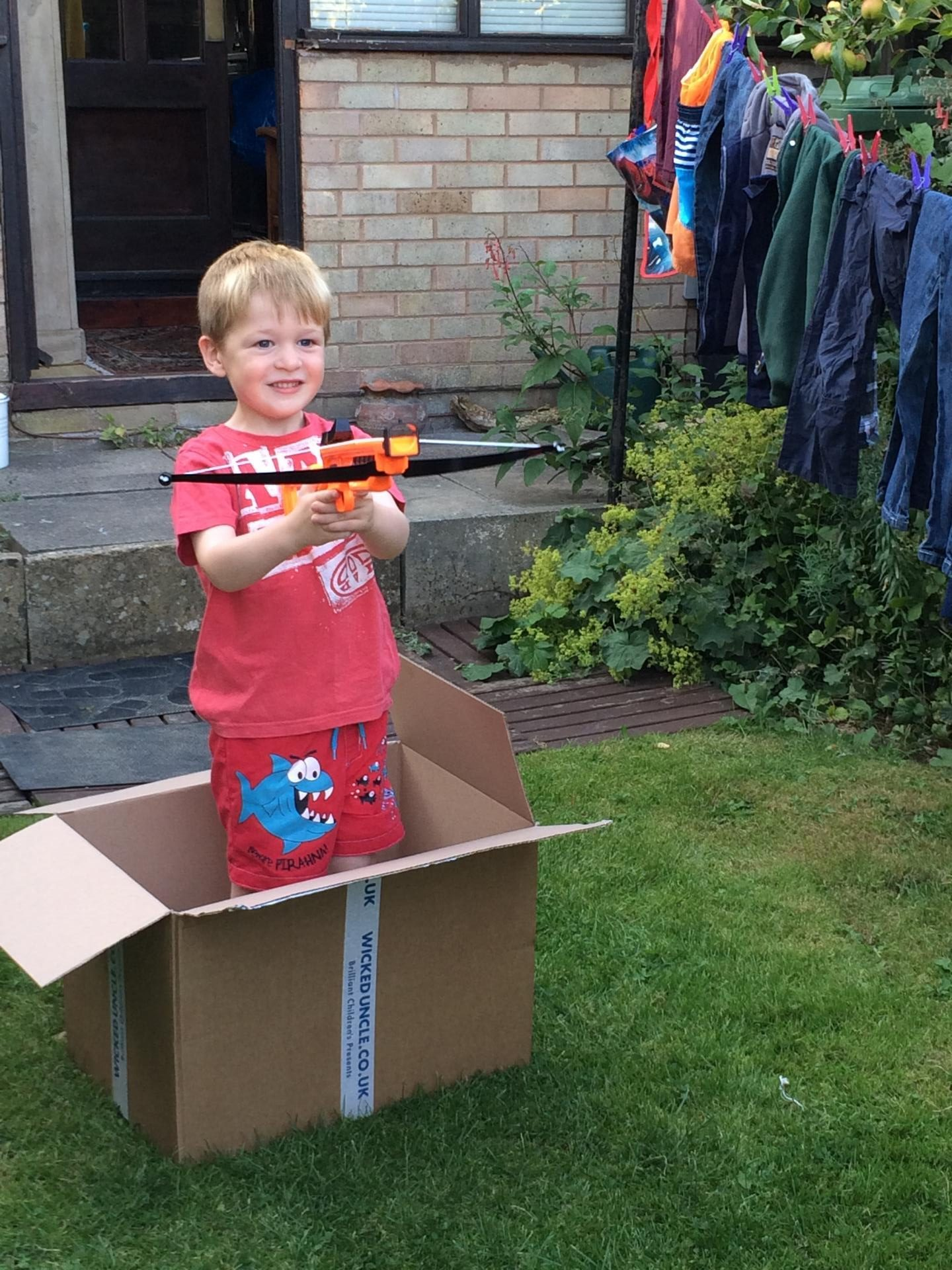 Boy sitting in a box with a handbow looking like he is trying to shoot someone.
