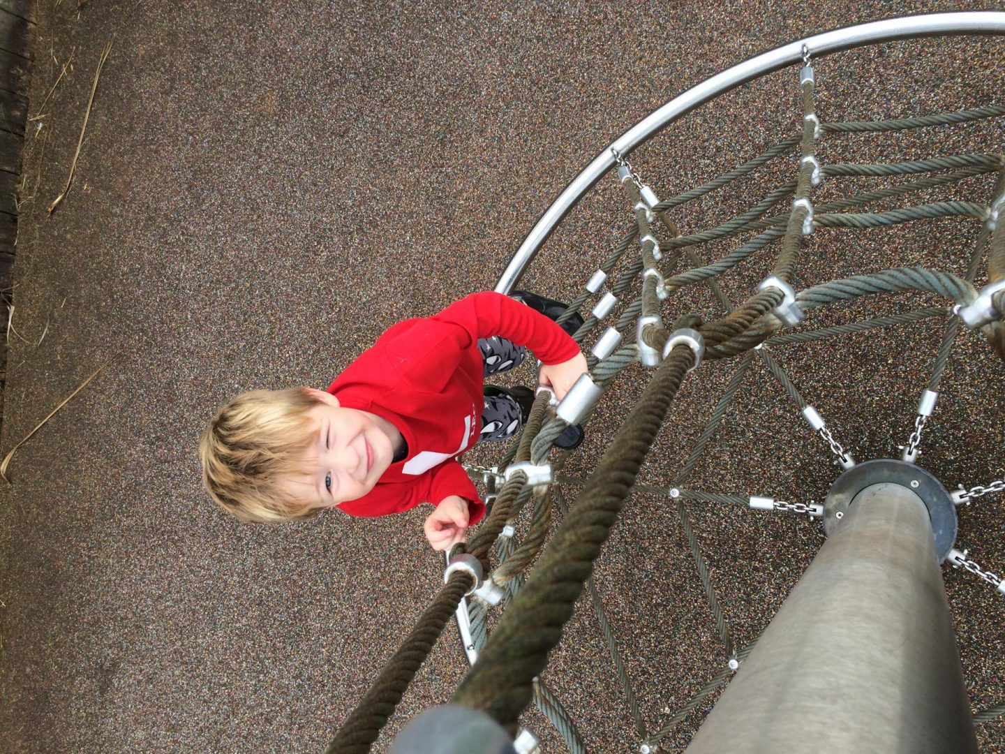 Picture taken from above of a little boy in a red top climbing up a climbing frame