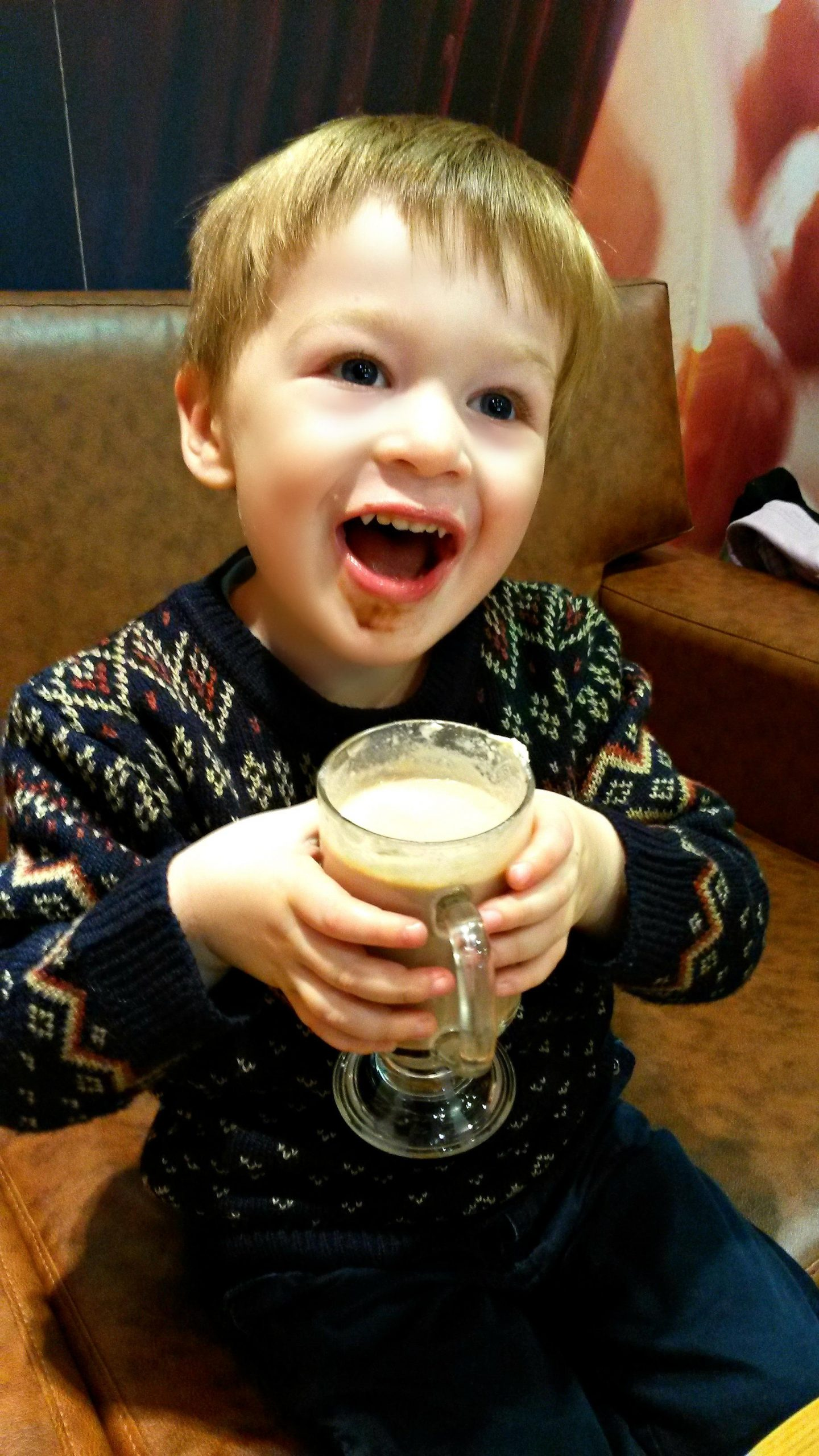 Little boy holding a cup and smiling