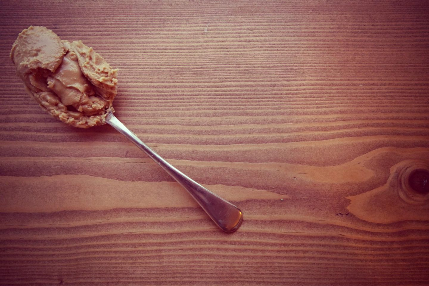 a wooden table with an old silver spoon on it covered in peanut butter