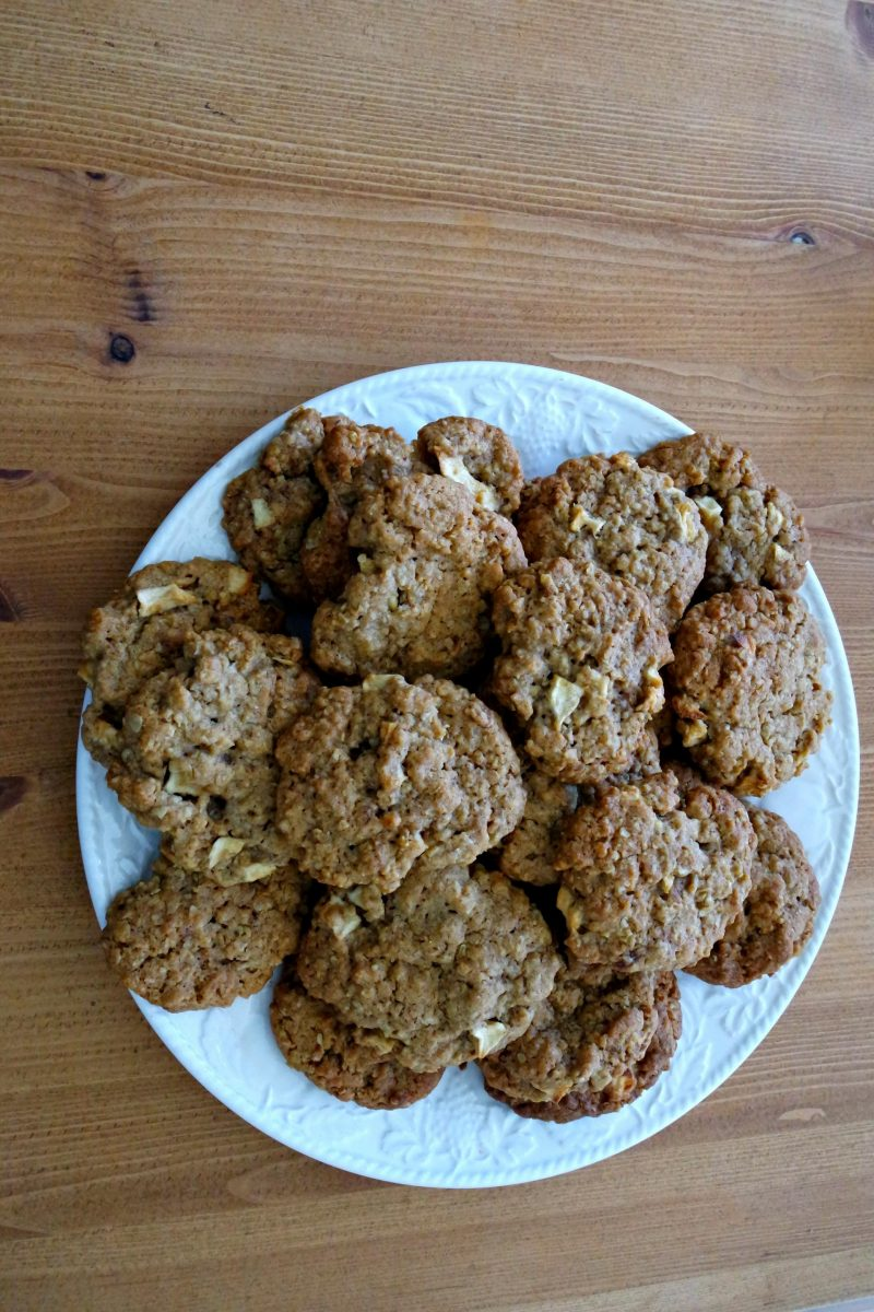 a white plate of cookies on a brown wooden table.