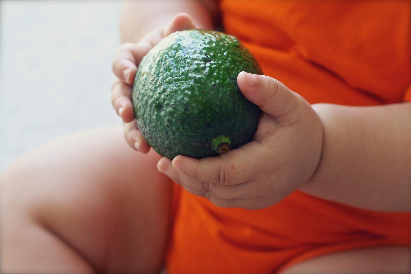 Close up of a green avacado and a child wearing a bright orange top