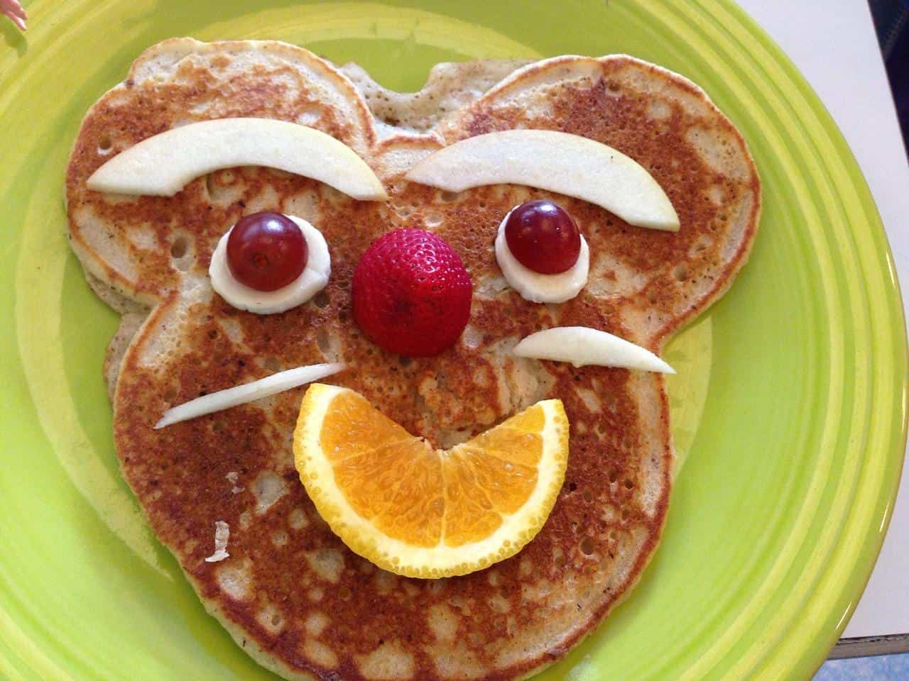 Pancake with grape eyes and orange mouth