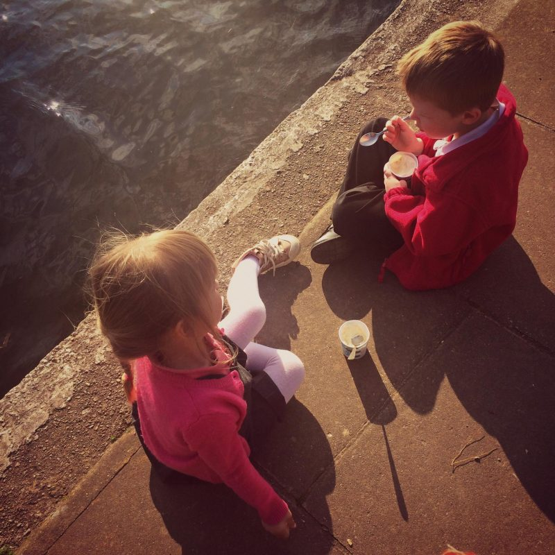 Two children sitting by the water