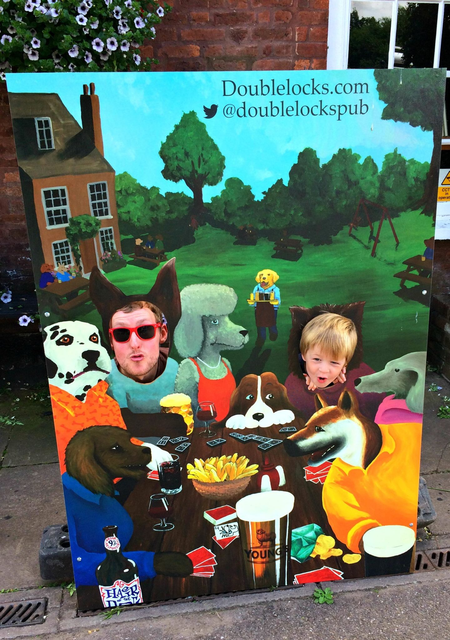 boy and dad standing behind a board painted with dogs
