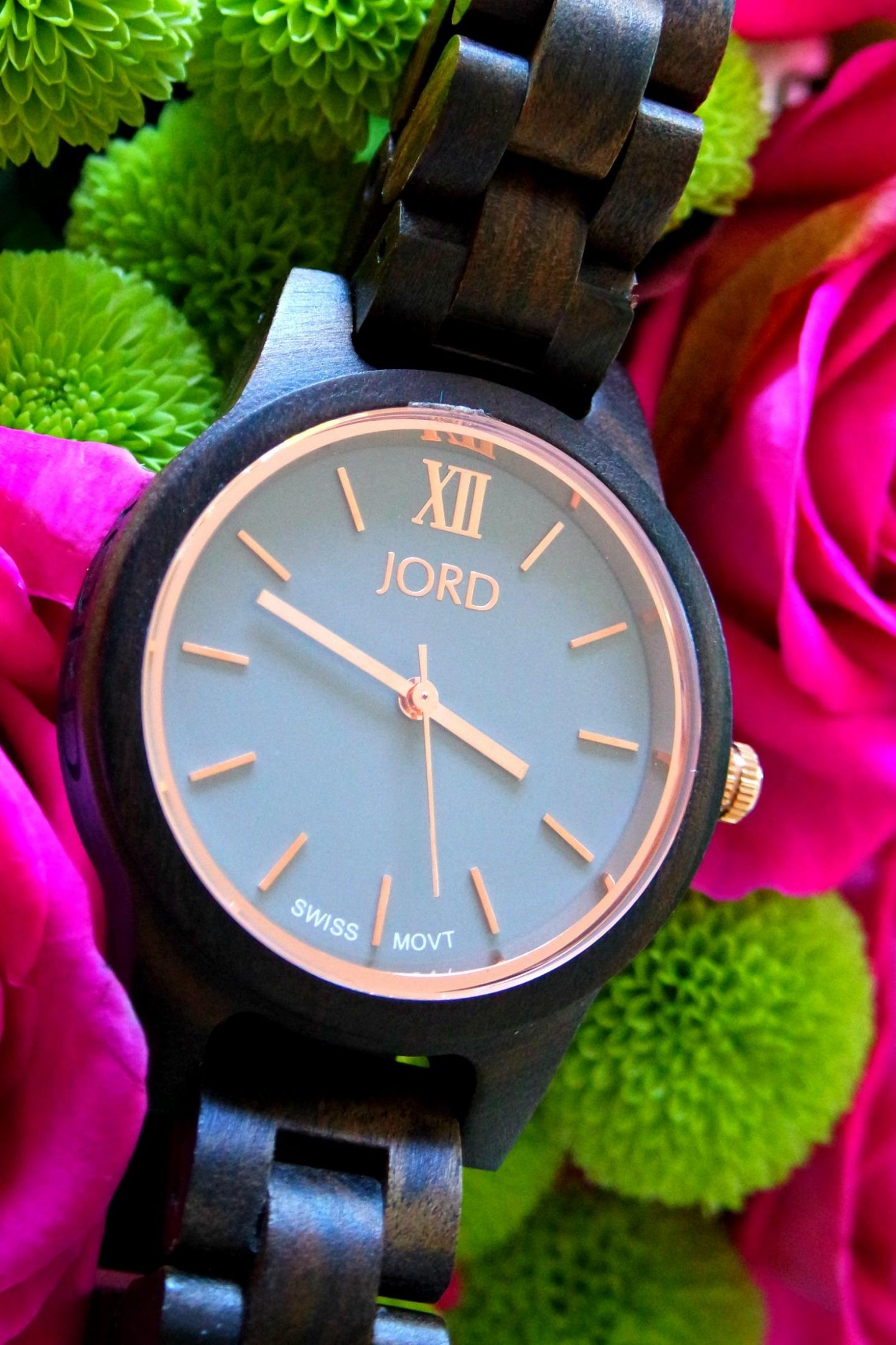 Close up photograph of a brown and purple watch made of wood resting on pink roses