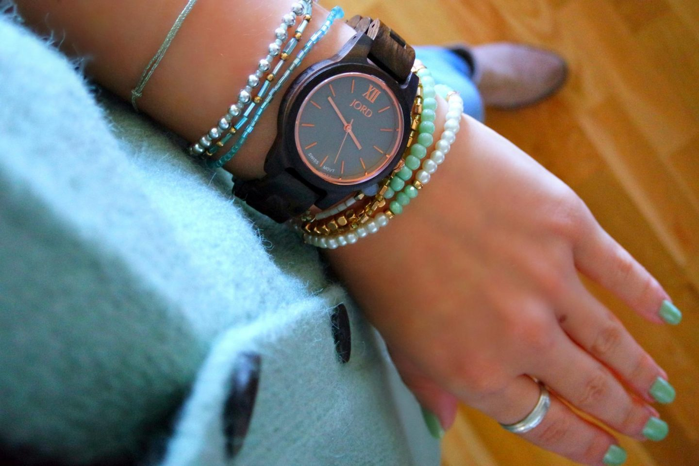 A brown wooden watch with a purply face on a wrist with turquoise bracelets and matching jumper