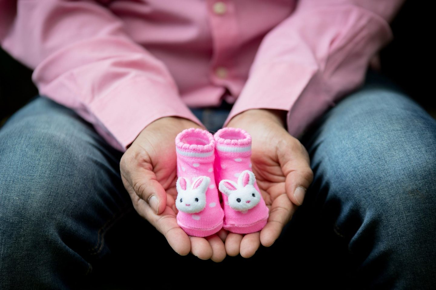 Picture of a man holding a pink pair of booties