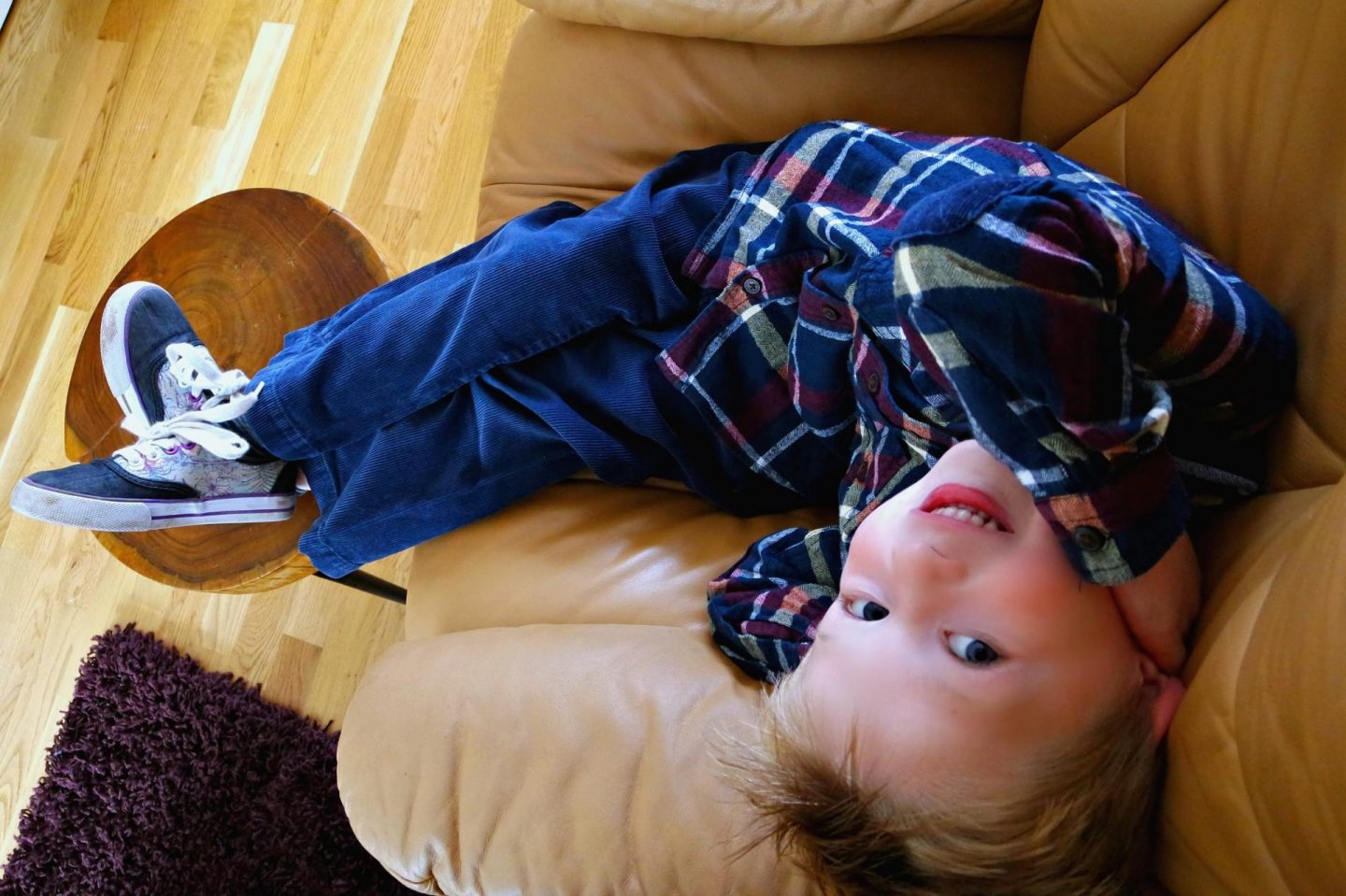 Little boy in blue jeans and shirt smiling, upside down at the camera.