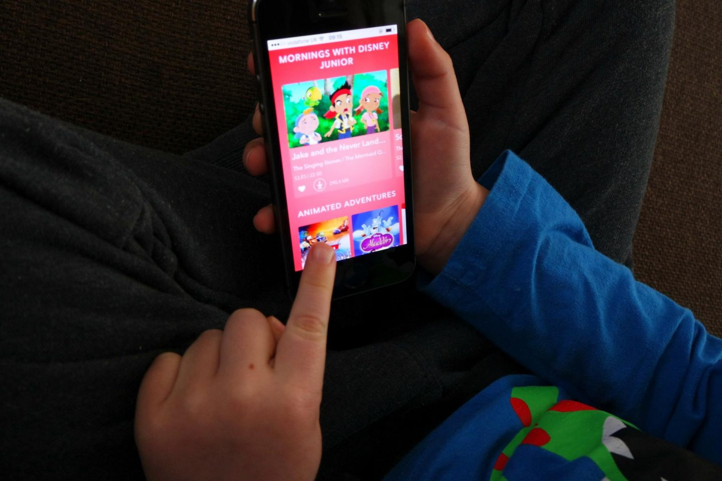 Boy playing with Disney app on phone