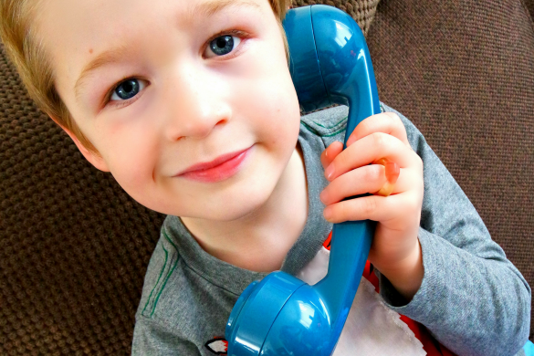 Boy holding a blue phone to his ear