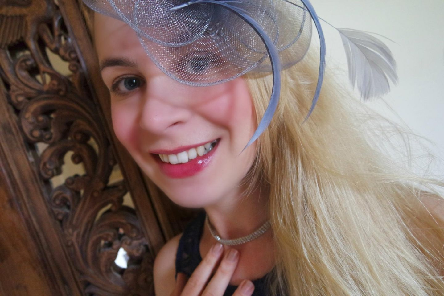 Blonde woman wearing grey fascinator