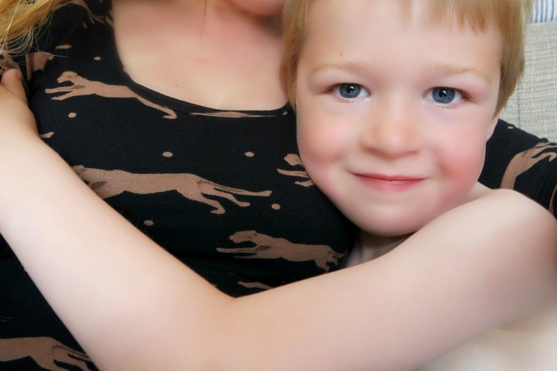 Little boy cuddling against his mums boobs.
