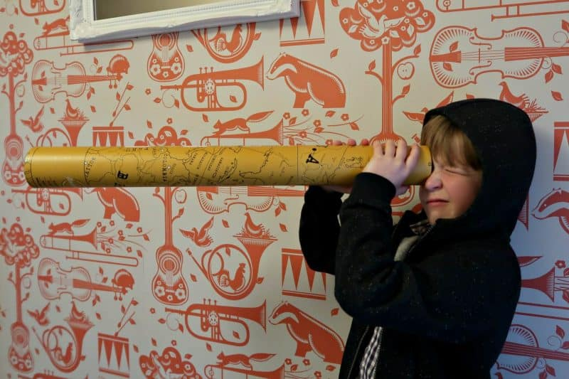 child holding scratch map gift in tube