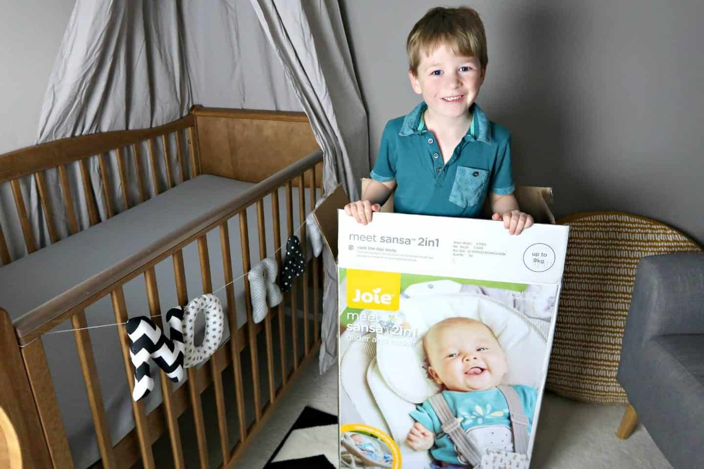 Smiling boy standing in a Joie Sansa 2 in 1 box