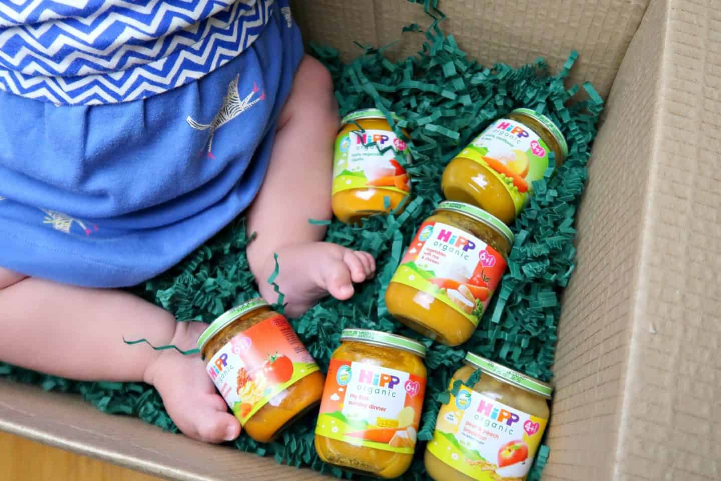HiPP babyfood jars in box by babies feet