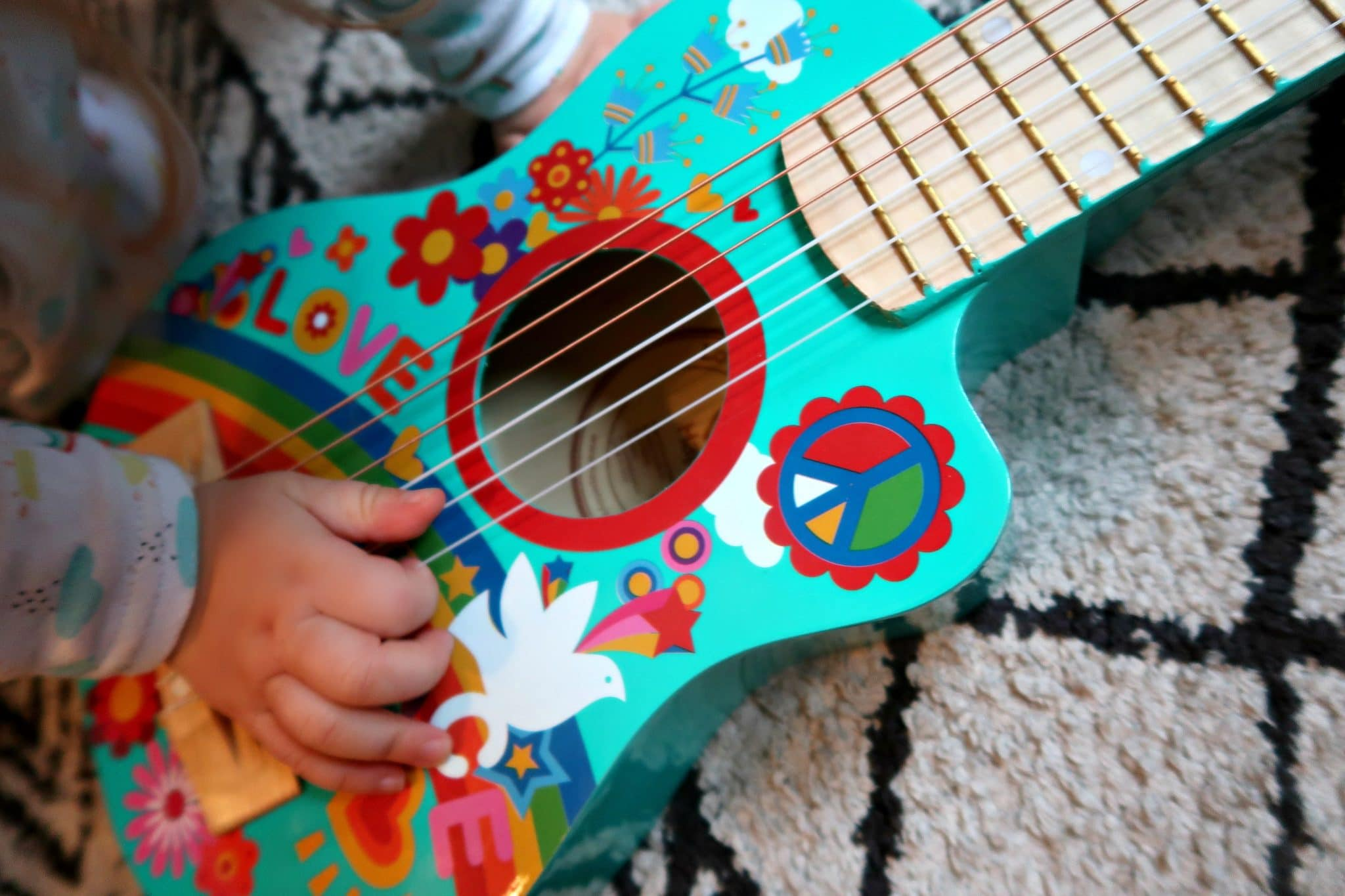 Close up of a small blue Hape wooden guitar with a babies hand on the strings
