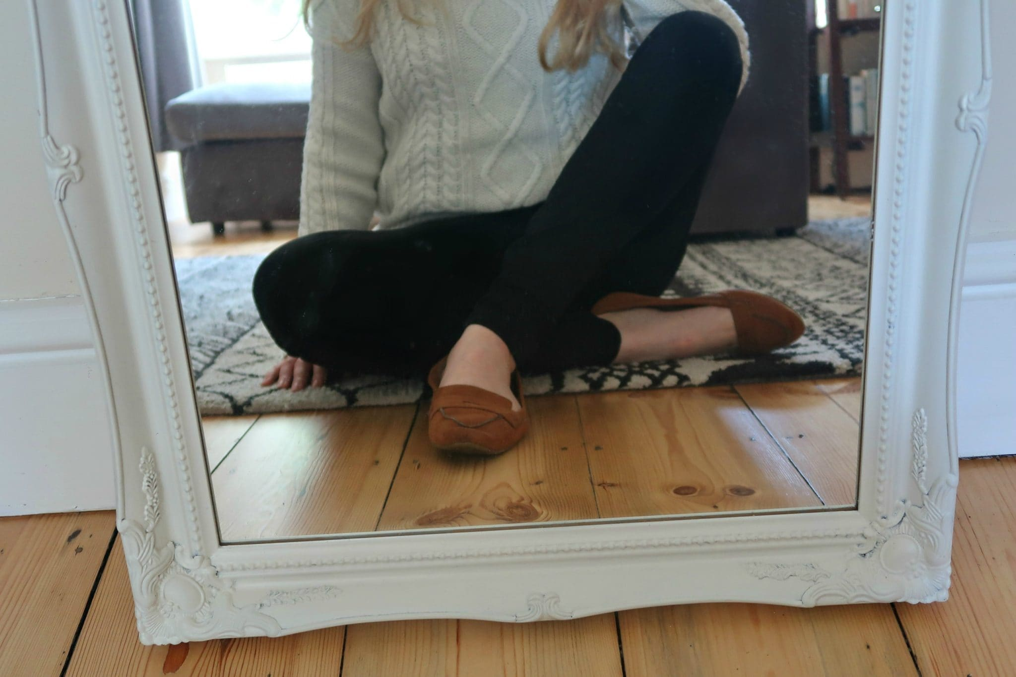 Do you want to Overhaul Your Wardrobe? White mirror with lady in black jeans sitting in the reflection