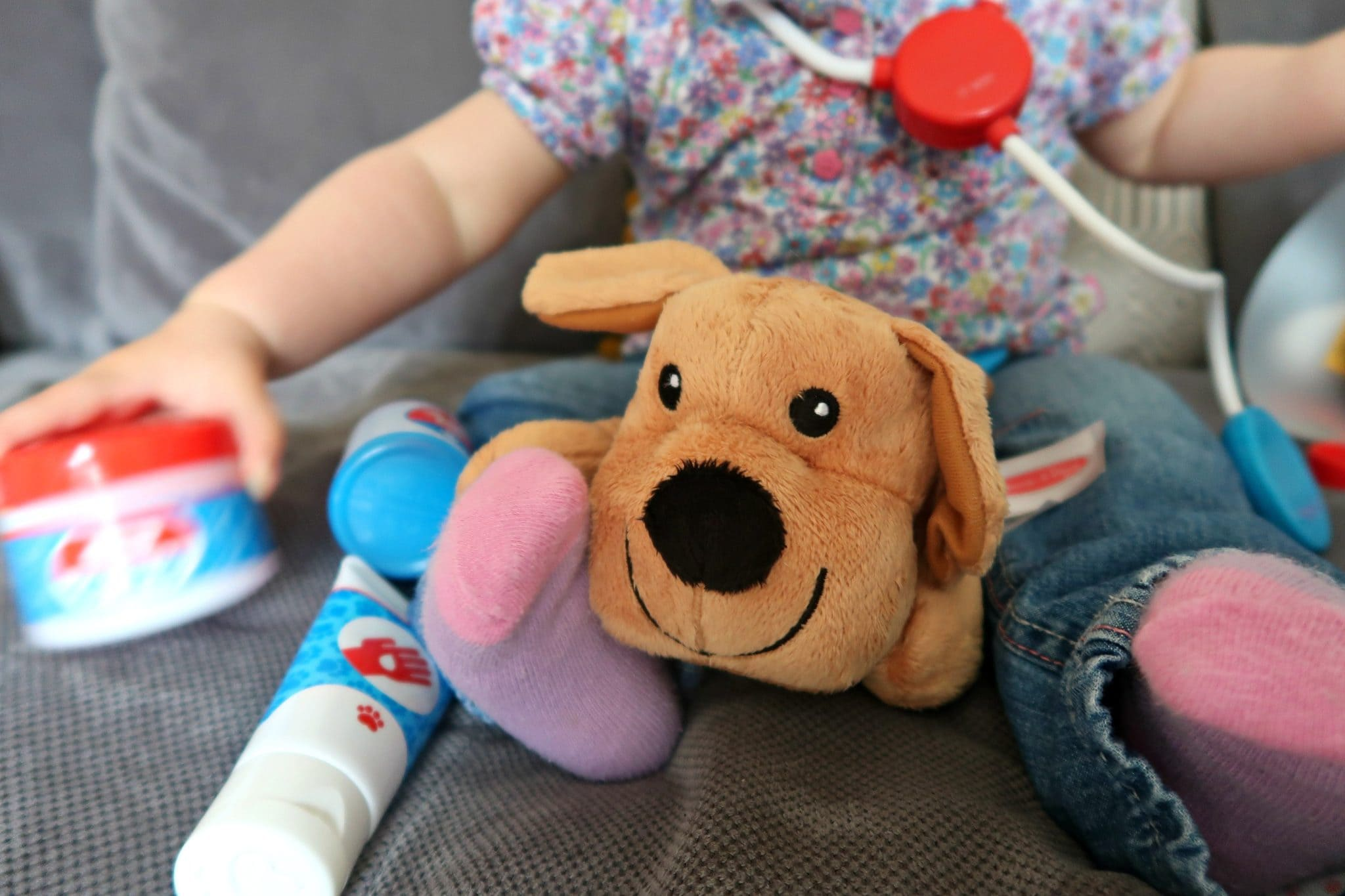 Close up of a toy puppy with plastic pretend vet toys besides it