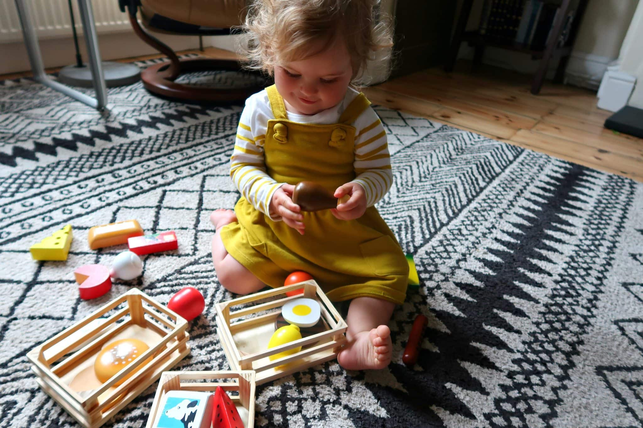 Little girl in a yellow dress smiling at wooden food in activities to do with your toddler