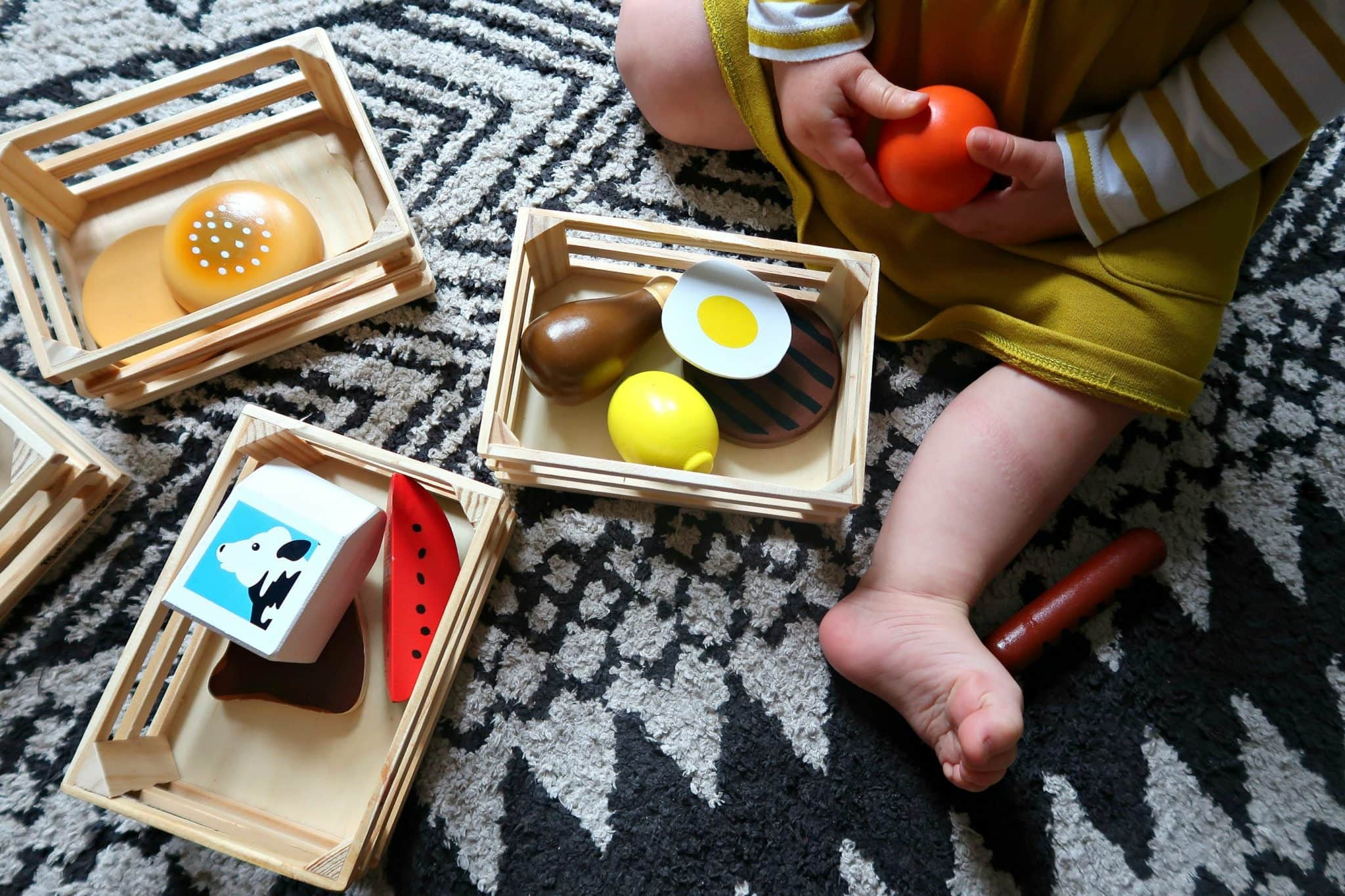 Close up of three wooden baskets of food and toddlers leg