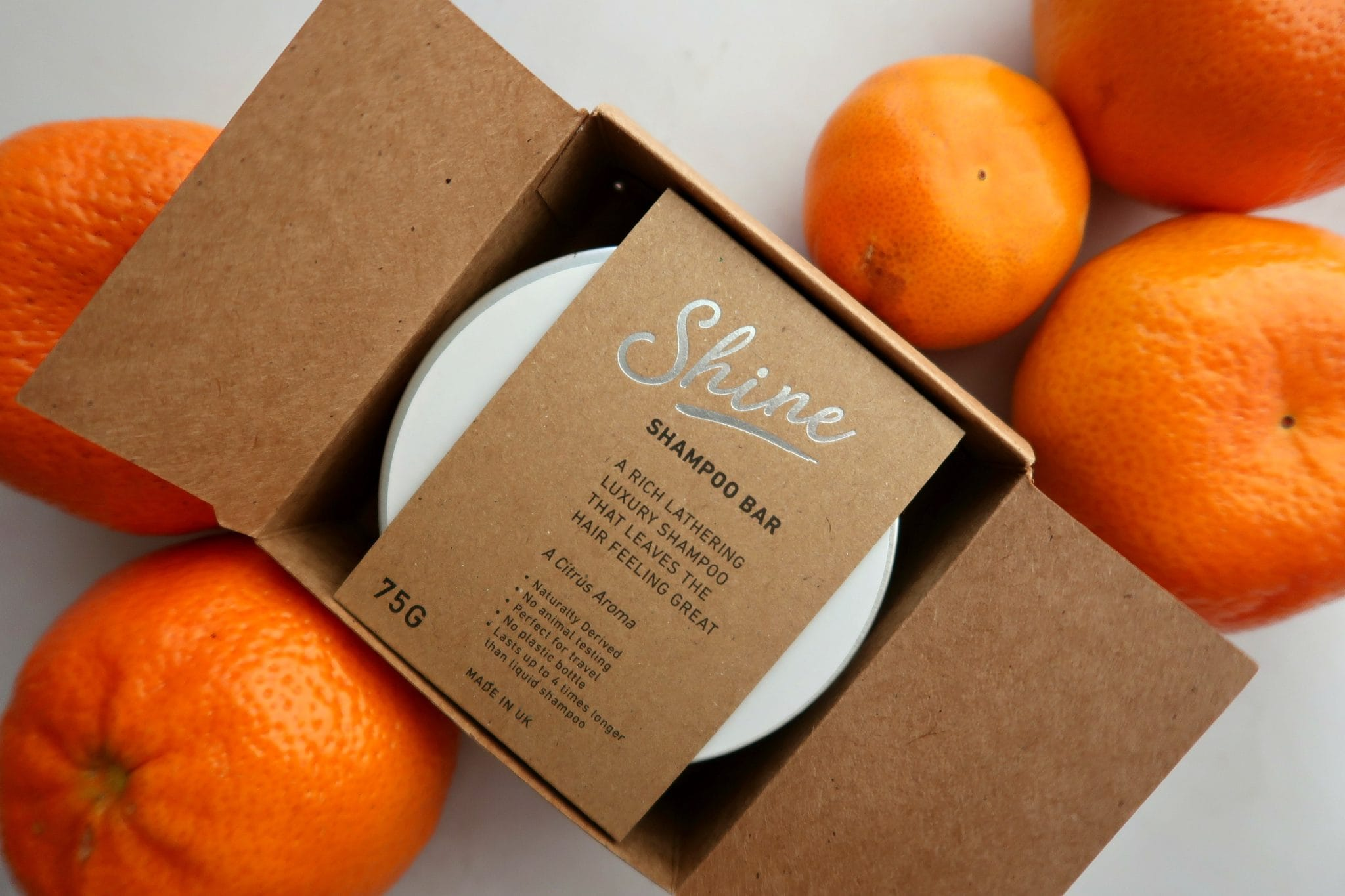 environmentally friendly living shine shampoo bar in a silver box surrownded by oranges