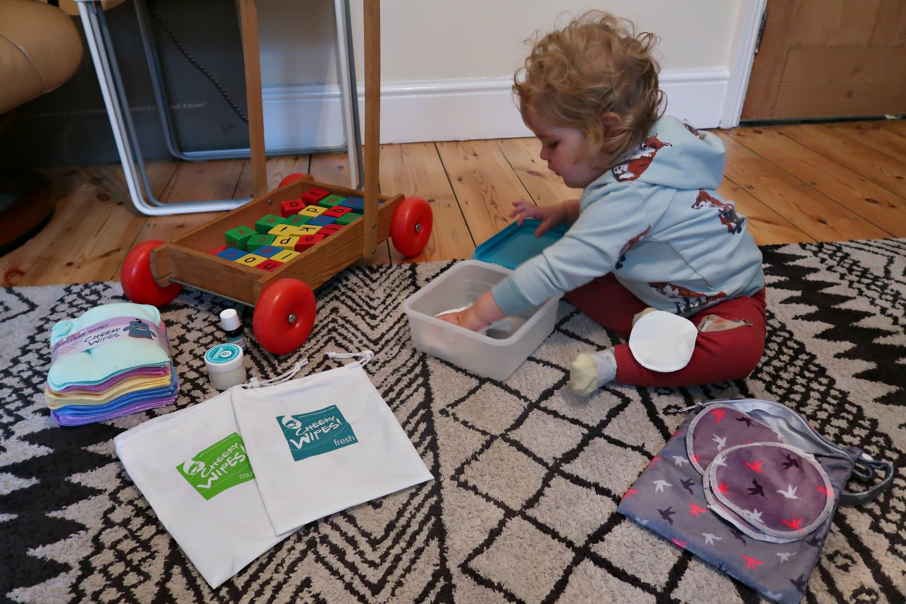 environmentally friendly living baby playing with cheeky wipes