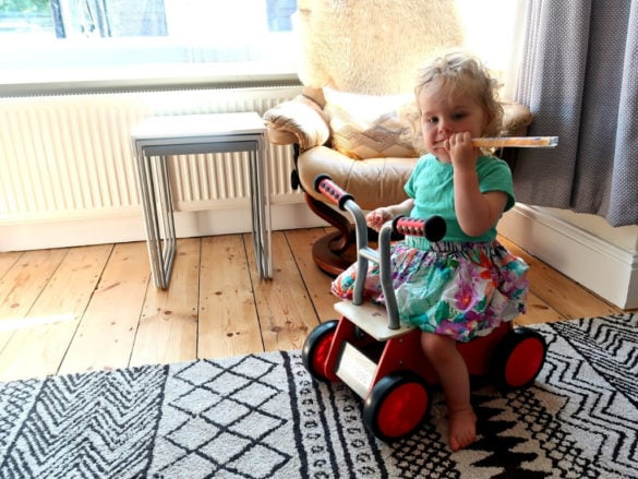 little girl sitting on the Hape red rider