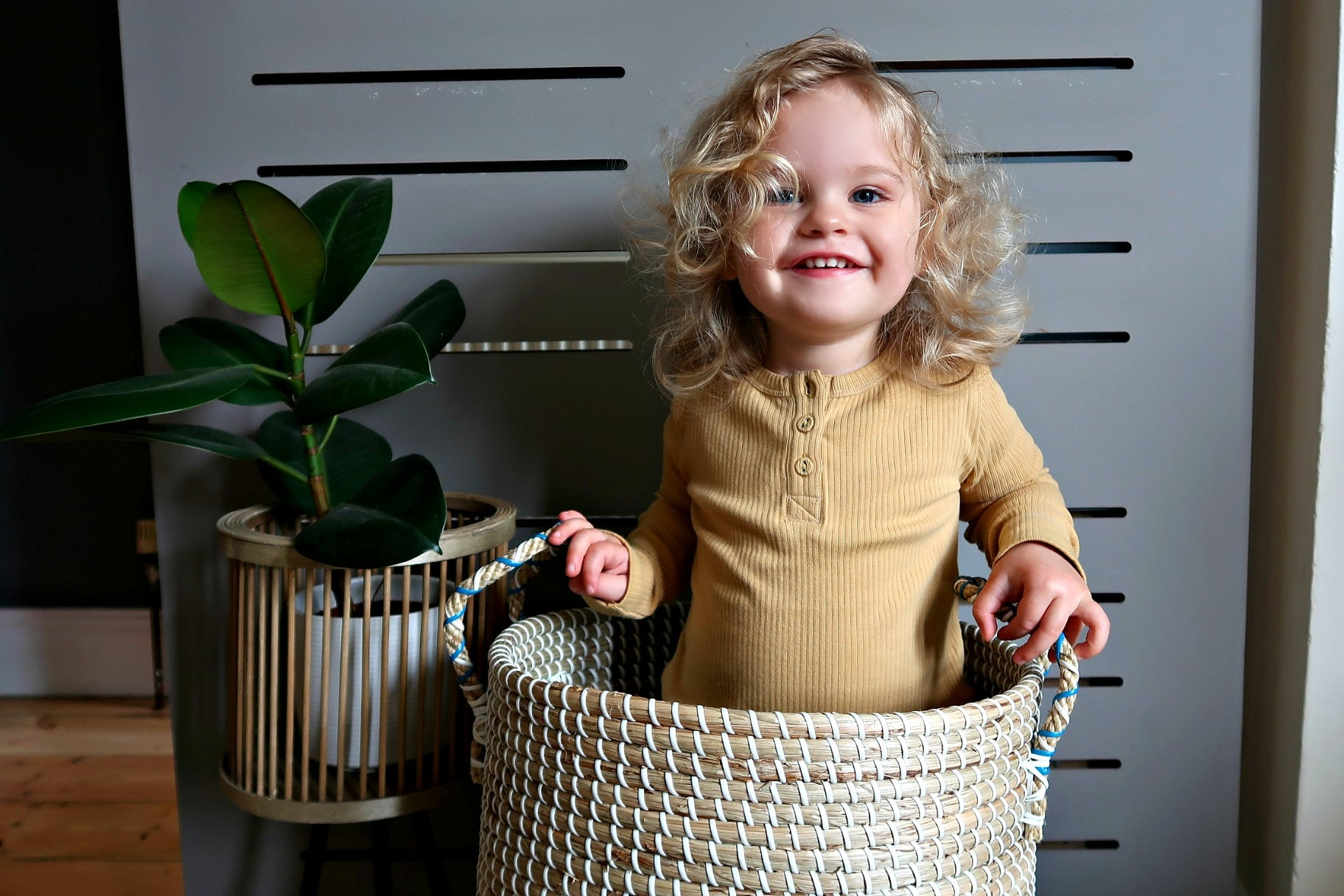 Girl with blonde hair sitting in a basket wearing an Oii mustard top.