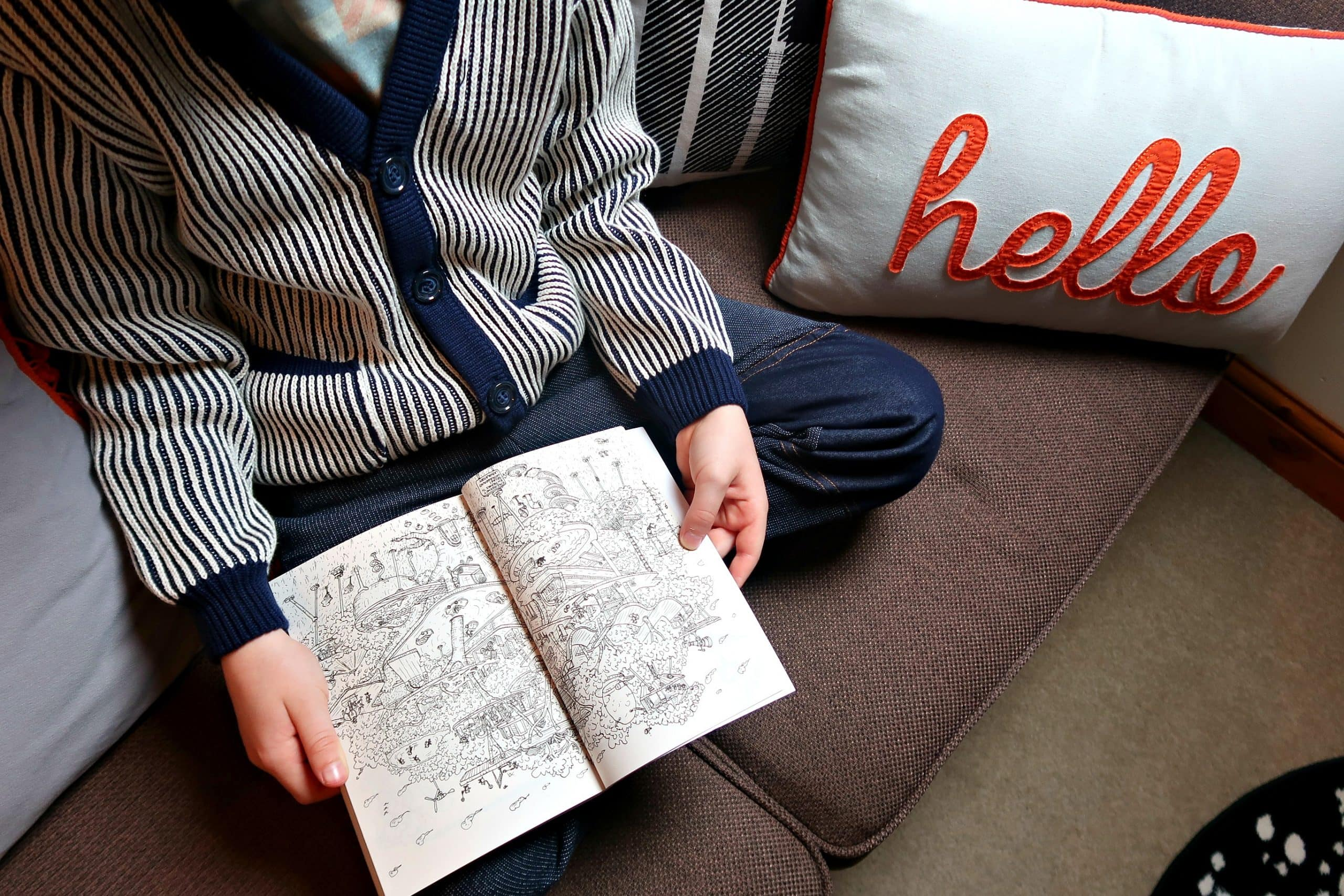 Close up of boy wearing blue and cream Oii jumper reading a book.