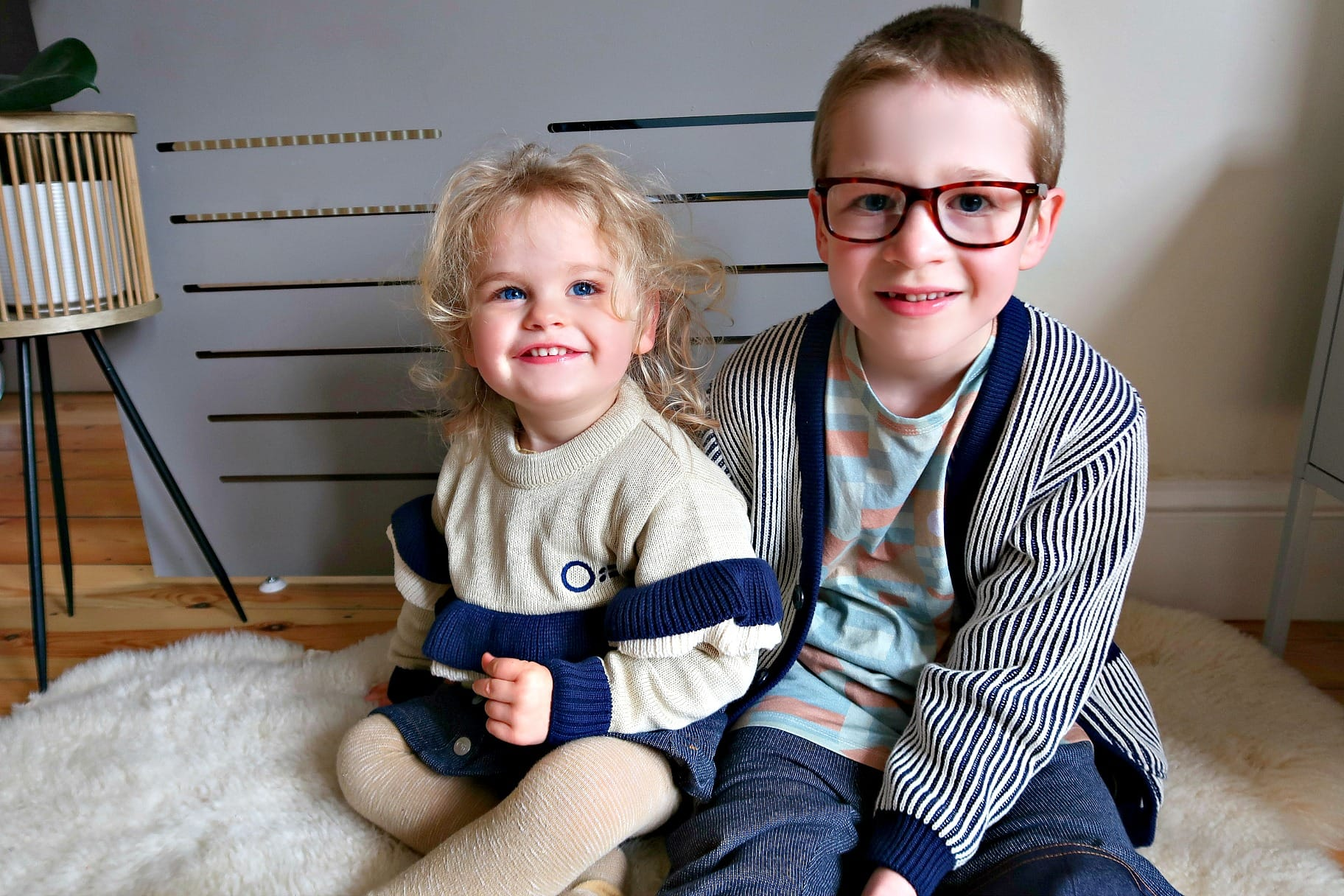 Two children wearing blue Oii outfits.
